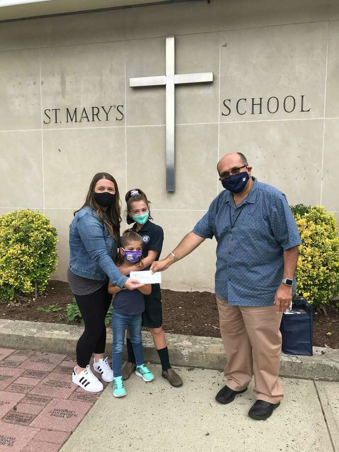 Danielle Hogan and her daughters Brooklyn and Devyn present a check for $1,000 from the St. Mary's pizza night fundraiser to Principal Deacon Dominic Corraro. Photo: Contributed / St Mary's School
