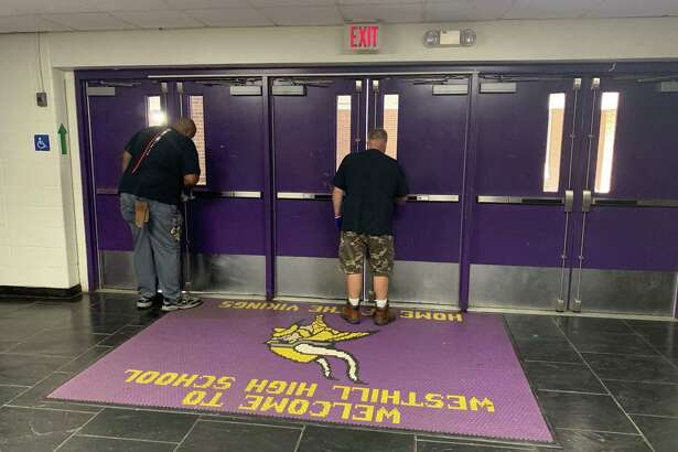 Custodians at Westhill High School wipe down doors inside the school on Friday, Sept. 25.