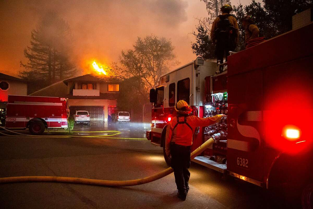 Firefighters spray down a home engulfed in fire on Beaumont Way in Santa Rosa on Monday.