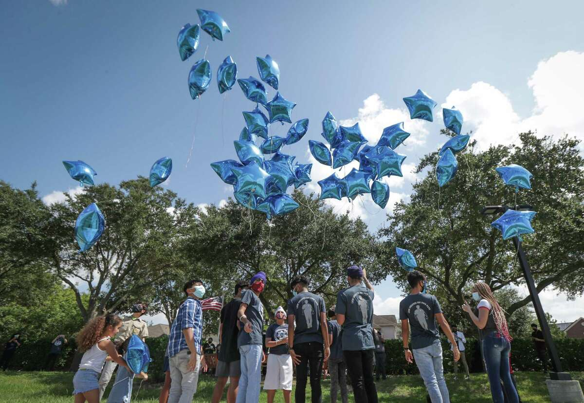 Children release balloons in honor of Harris County Sheriff's fallen Deputy Sandeep Singh Dhaliwal on the first anniversary of his death in Charles W. Austin Park Sunday, Sept. 27, 2020, in Houston.