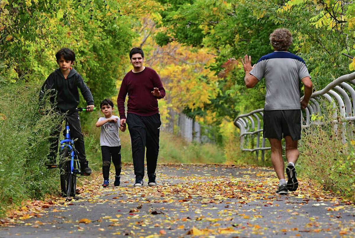 Ahmet Kaan Agsk of Albany, third from left, waves to a jogger as he walks with his nephews Emre Yildirim, 7, left, and Eren Yildirim, 5, on the Mohawk-Hudson Bike Path near the Corning Preserve on Monday, Sept. 28, 2020 in Albany, N.Y. (Lori Van Buren/Times Union)