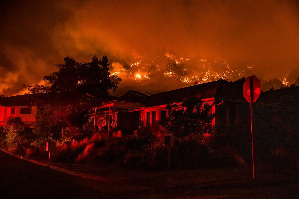 The Shady Fire can be seen on the hillside behind homes in Santa Rosa, on September 28, 2020. - The wildfire quickly spread over the mountains and reached Santa Rosa where it has begun to affect homes.