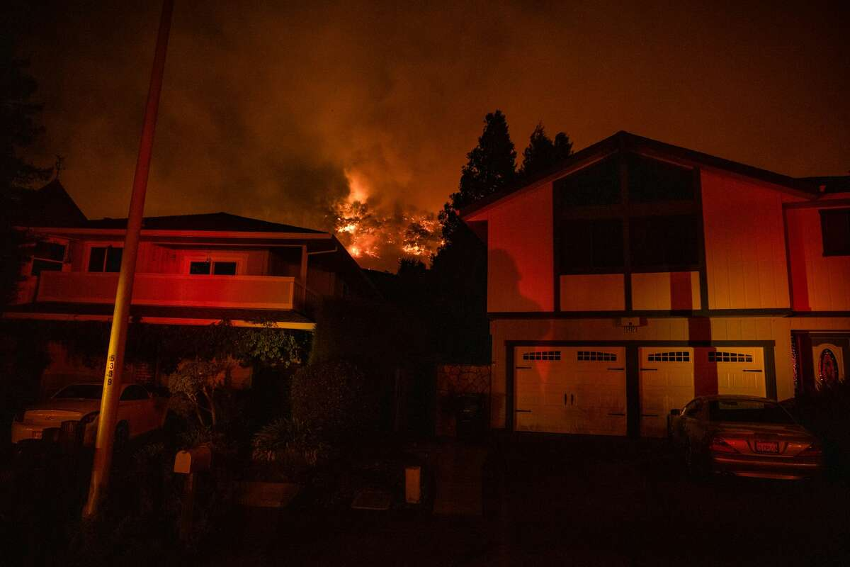 The Shady Fire can been seen on the hillside behind homes in Santa Rosa, California on September 28, 2020. - The wildfire quickly spread over the mountains and reached Santa Rosa where is has begun to affect homes.