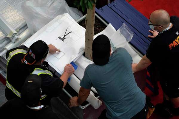 Workers hover over the blueprint of a camera riser ahead of the first presidential debate between Republican candidate President Donald Trump and Democratic candidate former Vice President Joe Biden at the Health Education Campus of Case Western Reserve University, Monday, Sept. 28, 2020, in Cleveland. (AP Photo/Julio Cortez)