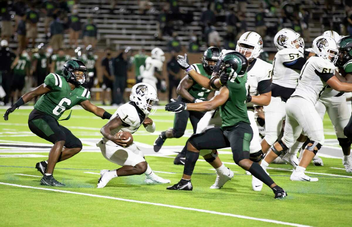 Conroe quarterback Jalen Williams (1) gets pulled by Mayde Creek defensive back Kevin Earls III (6) during the fourth quarter of a non-district football game at Rhodes Stadium in Katy, Friday, Sept. 25, 2020.