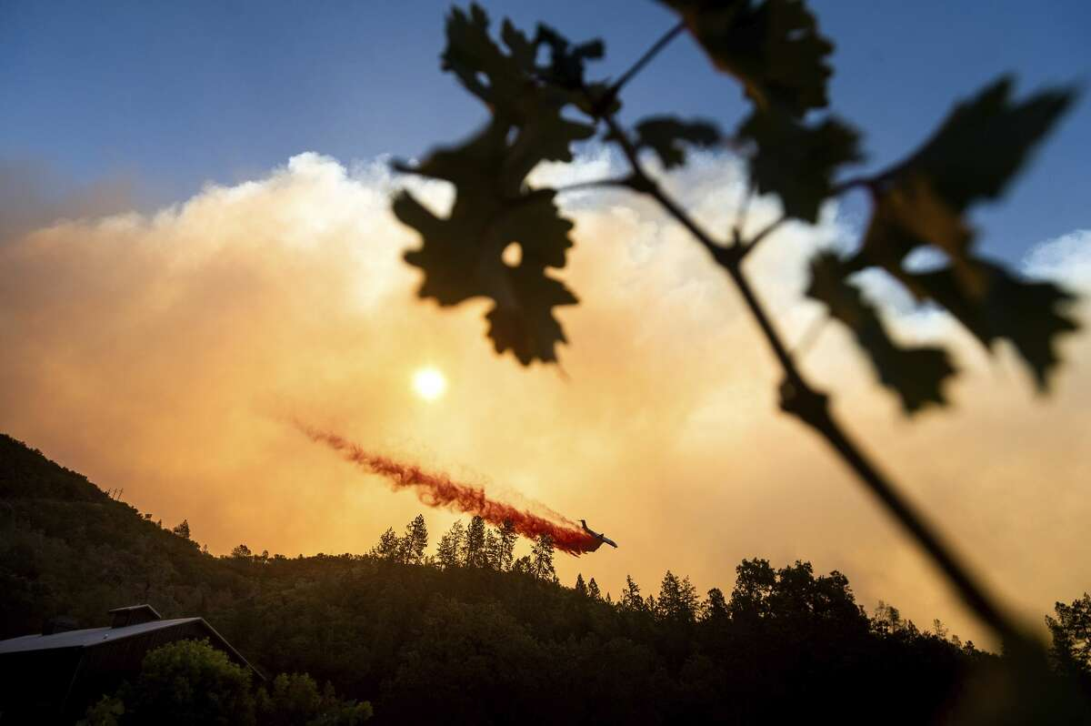 An air tanker drops retardant on the Glass Fire burning above Davis Estates winery in Calistoga, Calif., on Sunday, Sept. 27, 2020.