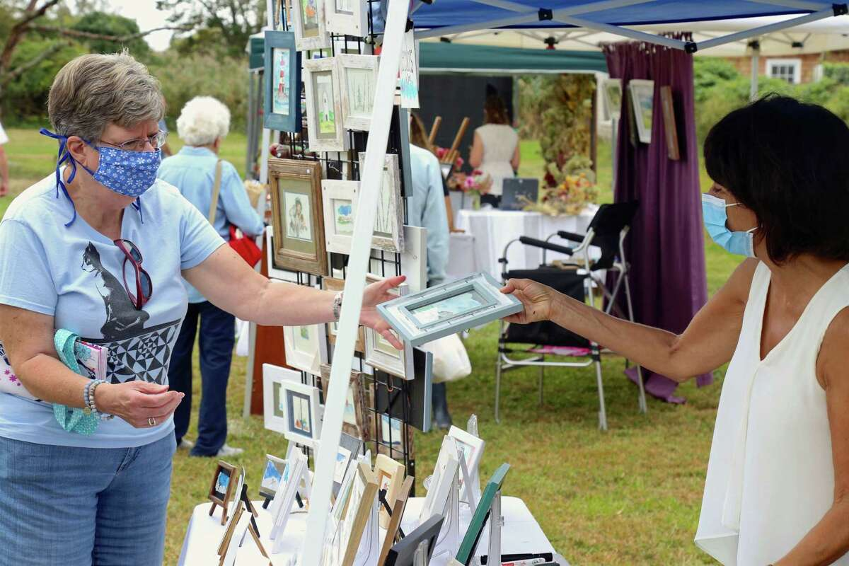 Debbie Wooley of Hamden purchases a painting by Donna Albano of Danbury at the Scandinavian Club's Arts & Crafts Fair on Sunday, Sept. 27, 2020, in Fairfield, Conn.