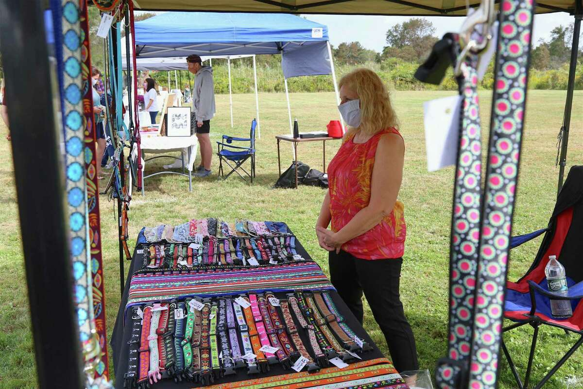 Sue Fow of Redding-based Stephanie Lauren stands amidst her dog collar and leash creations at the Scandinavian Club's Arts & Crafts Fair on Sunday, Sept. 27, 2020, in Fairfield, Conn.