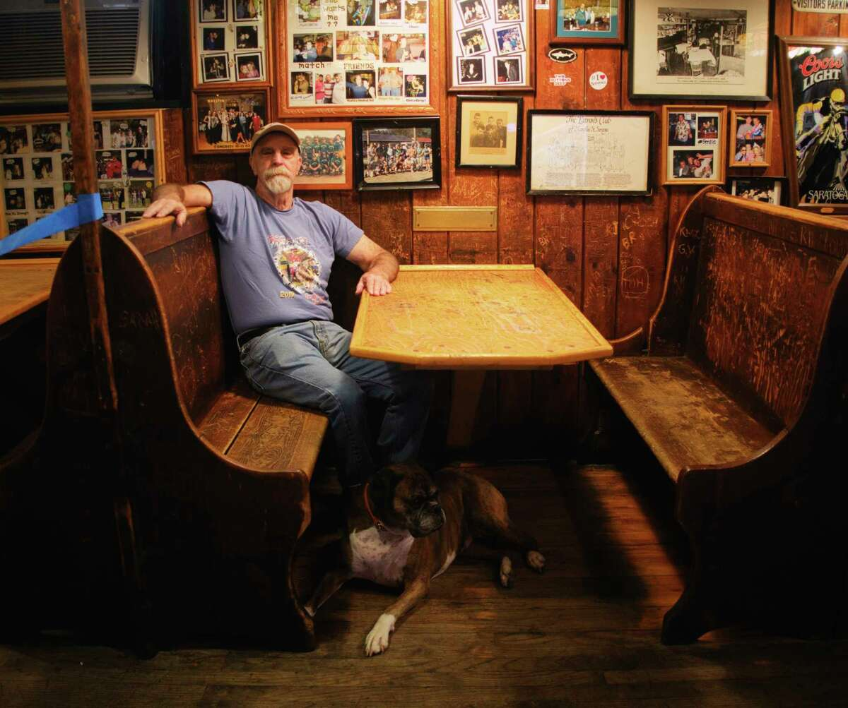 Tin & Lint owner Jim Stanley in his bar with his dog Scarlett on Wednesday, Sept. 23, 2020, in Saratoga Springs, N.Y. Stanley is sitting in the booth where musician Don McLean began writing the song American Pie one night in the summer of 1970. (Paul Buckowski/Times Union)