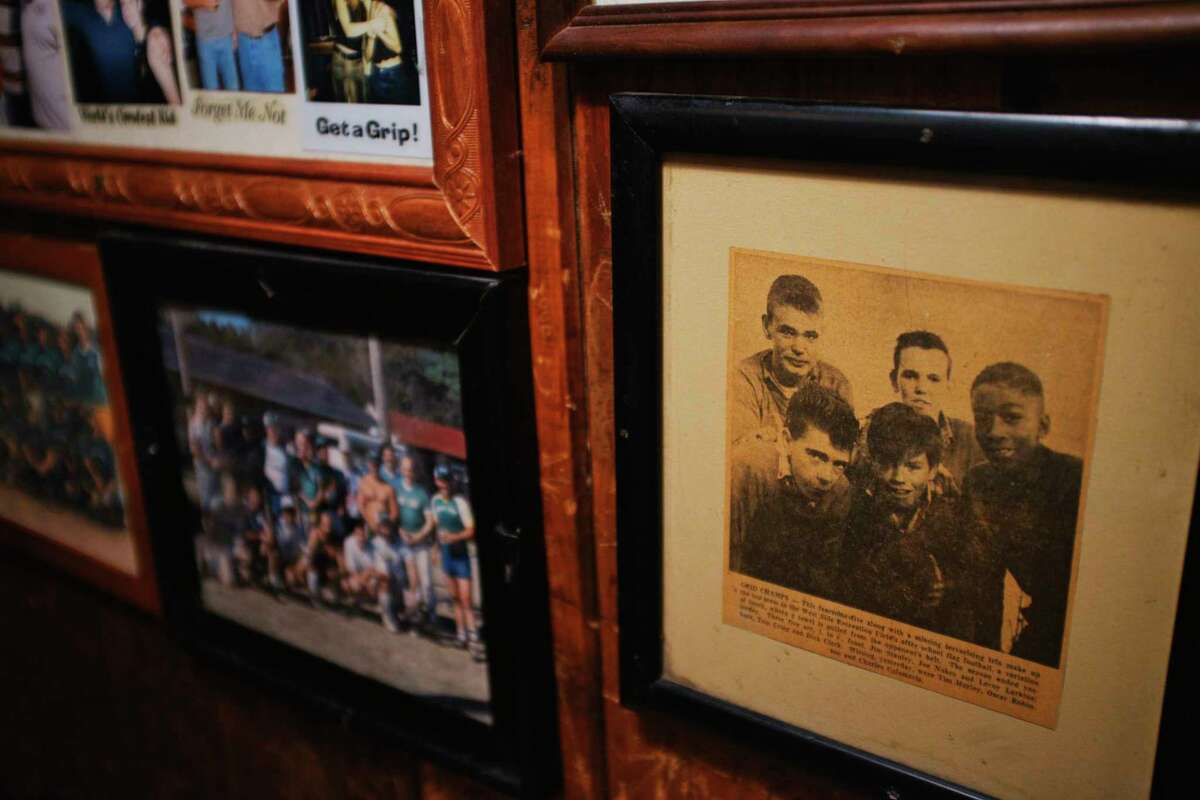 An old newspaper clipping on the wall inside the Tin & Lint shows a image of bar owner Jim Stanley, bottom left, when he was a young boy. The boys were champions of a flag football league. (Paul Buckowski/Times Union)