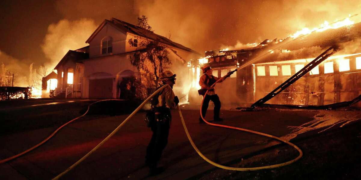 Firefighters try to keep house fires from spreading on Mountain Hawk Wayin the Skyhawk area of Santa Rosa on Monday.