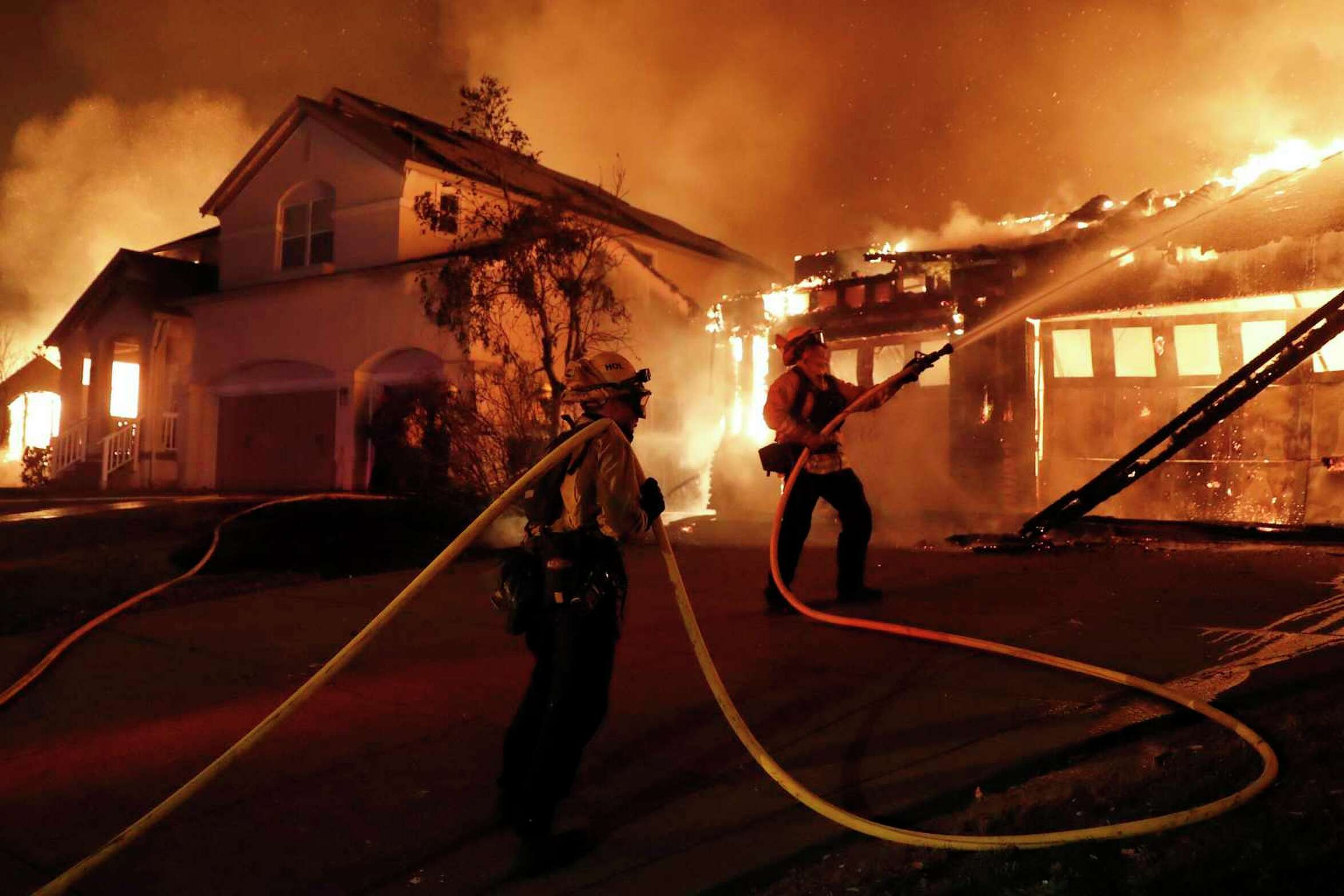 Firefighters try to keep house fires from spreading on Mountain Hawk Way as the Shady Fire burns in Skyhawk area of Santa Rosa, Calif., on Monday, September 28, 2020.