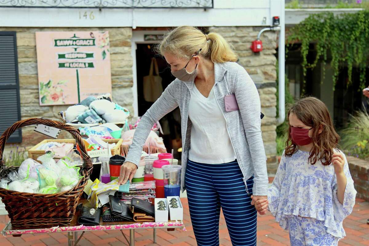 Caroline Hammond of Westport and her daughter Weatherly, 7, check out some items at Savvy+Grace during the Fall Fashion & Beauty Day downtown on Saturday, Sept. 26, 2020, in Westport, Conn.