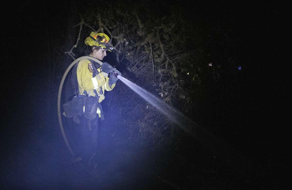 A Cal Fire firefighter douses hot spots the Zogg Fire near Igo, Calif., on Sunday, Sep. 27, 2020.
