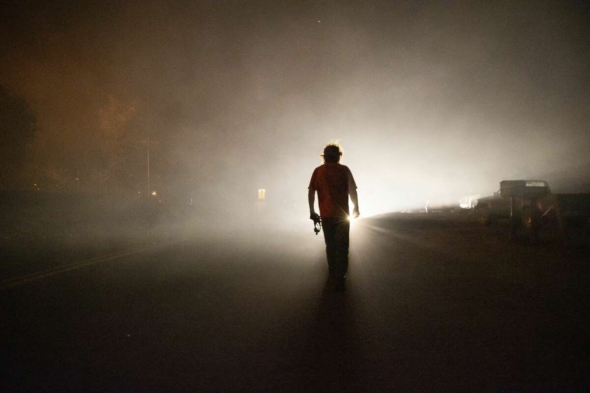 Tom Smith walks on Platina Road after refusing to evacuate from the Zogg Fire near Ono, Calif., on Sunday, Sep. 27, 2020.