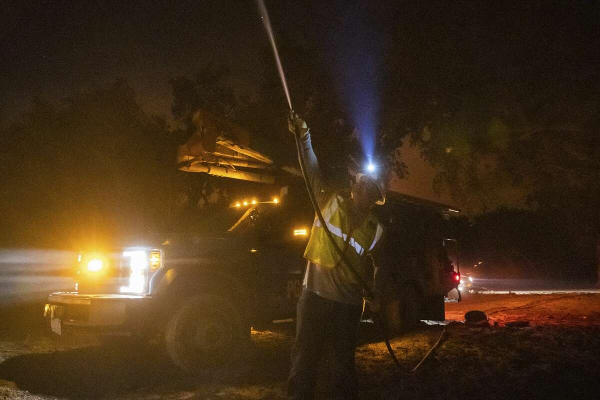 PG&E employee Sean Ohaire hoses down a telephone pole at the Zogg Fire near Igo, Calif., early Monday, Sep. 28, 2020.