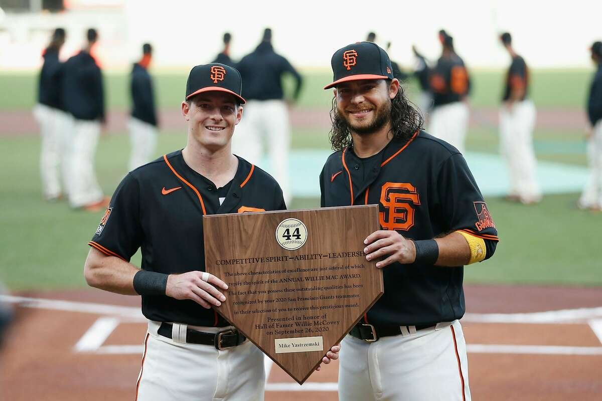 Mike Yastrzemski is presented with the Giants' 2020 Willie Mac Award by teammate Brandon Crawford before Saturday's game against the San Diego Padres.