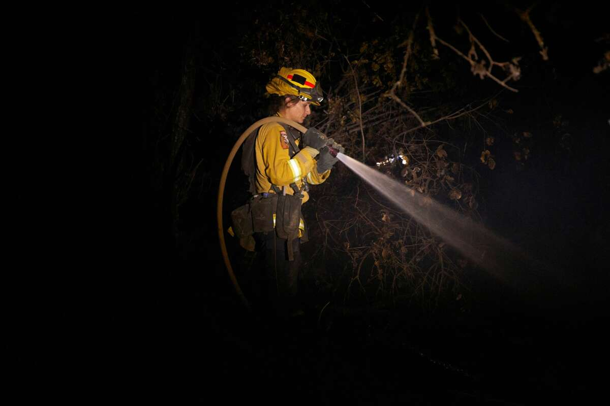 A fire fighter puts out hot spots from the Zogg fire in Igo on September 27, 2020.