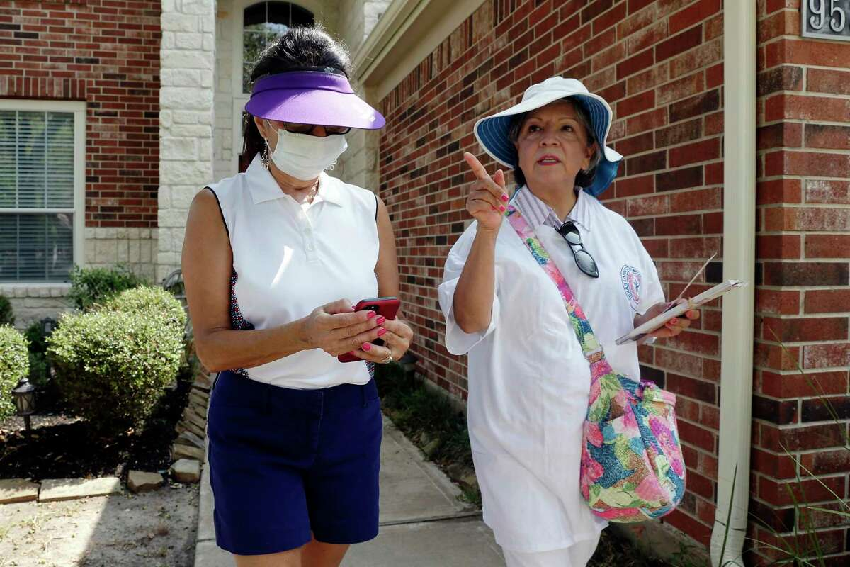 Volunteers with Texas Latino Conservatives Alicia Stuart, left, and Grace Aguilar, right, ring door bells and hang political brochures on door knobs as they block-walk for GOP House district candidate Justin Ray in a residential subdivision Saturday, Sep. 19, 2020 in Cypress, TX.