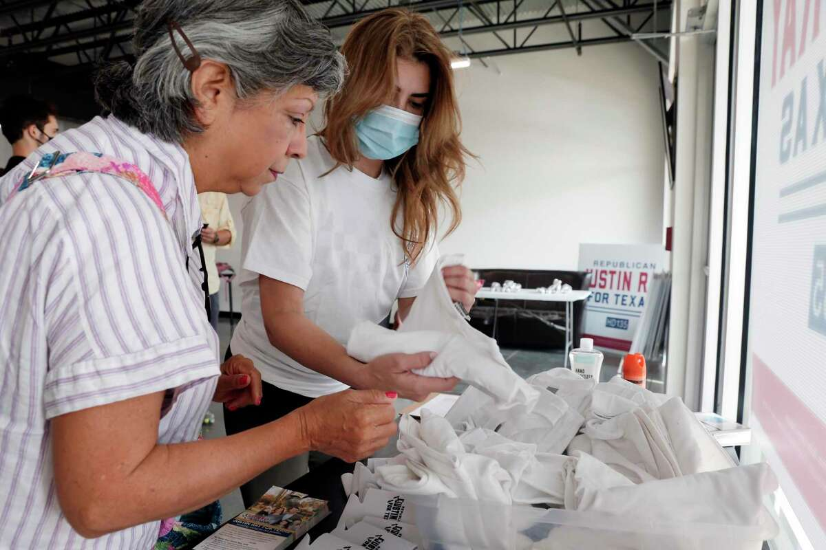 Texas Latino Conservatives campaign workers Grace Aguilar, left, and Andrea Gomez search for their size t-shirts at the Justin Ray campaign headquarters before they and other volunteers head out to block-walk for Ray in a residential subdivision Saturday, Sep. 19, 2020 in Cypress, TX.