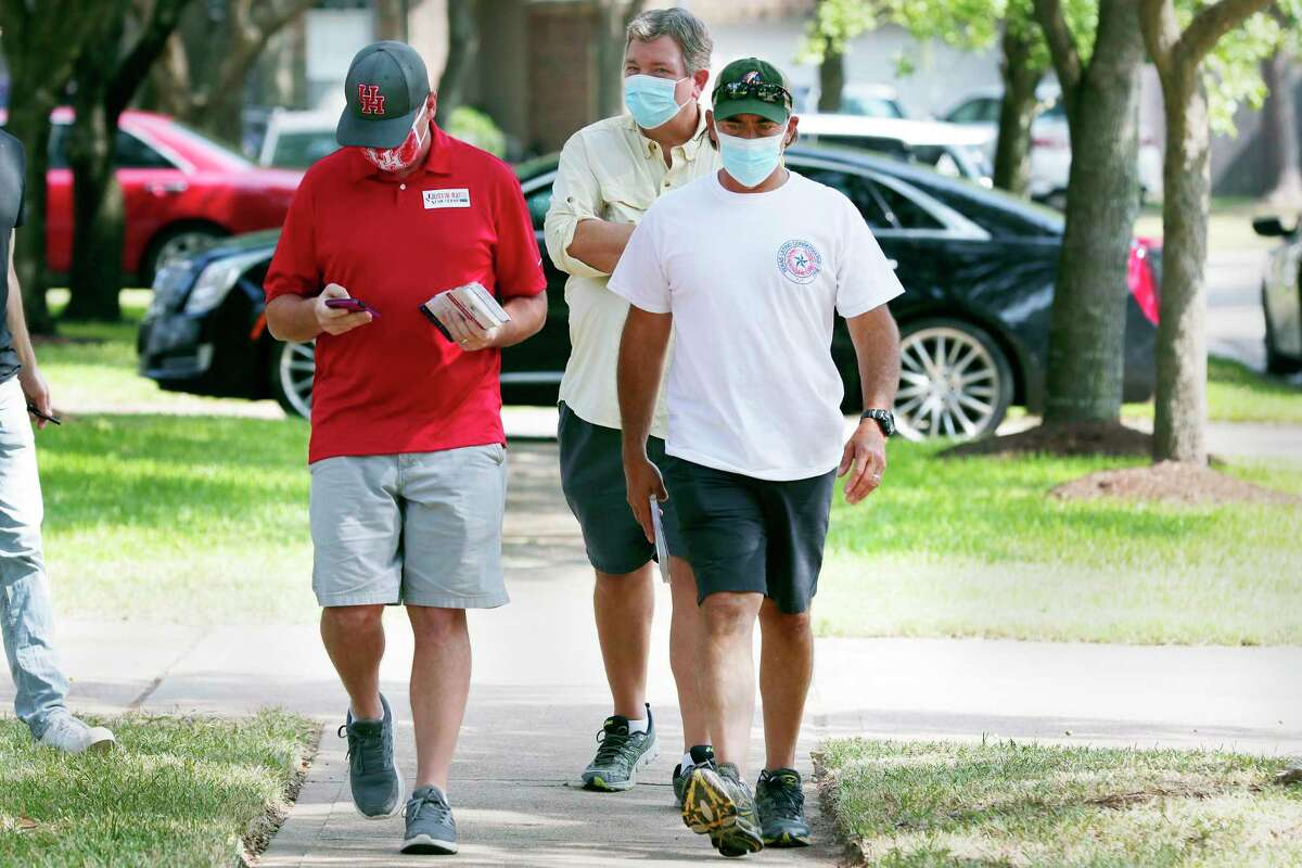 From left, candidate Justin Ray, volunteer Chris Beavers and Orlando Sanchez, founder of Texas Latino Conservatives block-walk for Ray in a residential subdivision Saturday, Sep. 19, 2020 in Cypress, TX.
