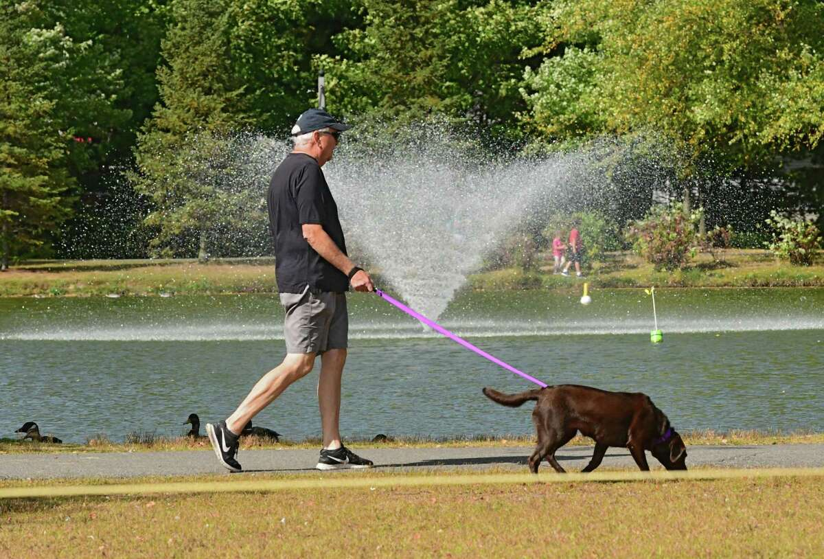 A man walks a dog around the pond at The Crossings of Colonie on Monday, Sept. 28, 2020 in Colonie, N.Y. (Lori Van Buren/Times Union)