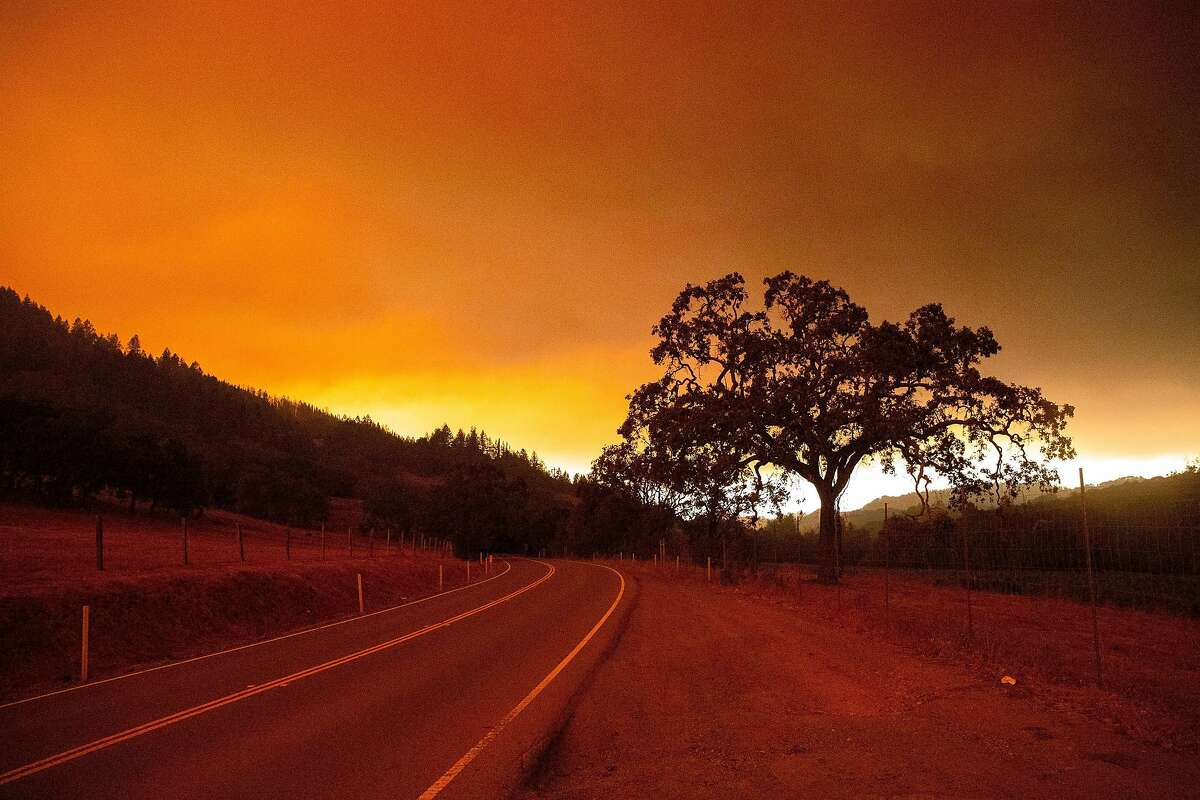 Smoke hangs above the horizon as the sun peaks from behind it on Calistoga Drive during the Glass Fire in Calistoga, Calif. on Monday morning, Sept. 28, 2020.