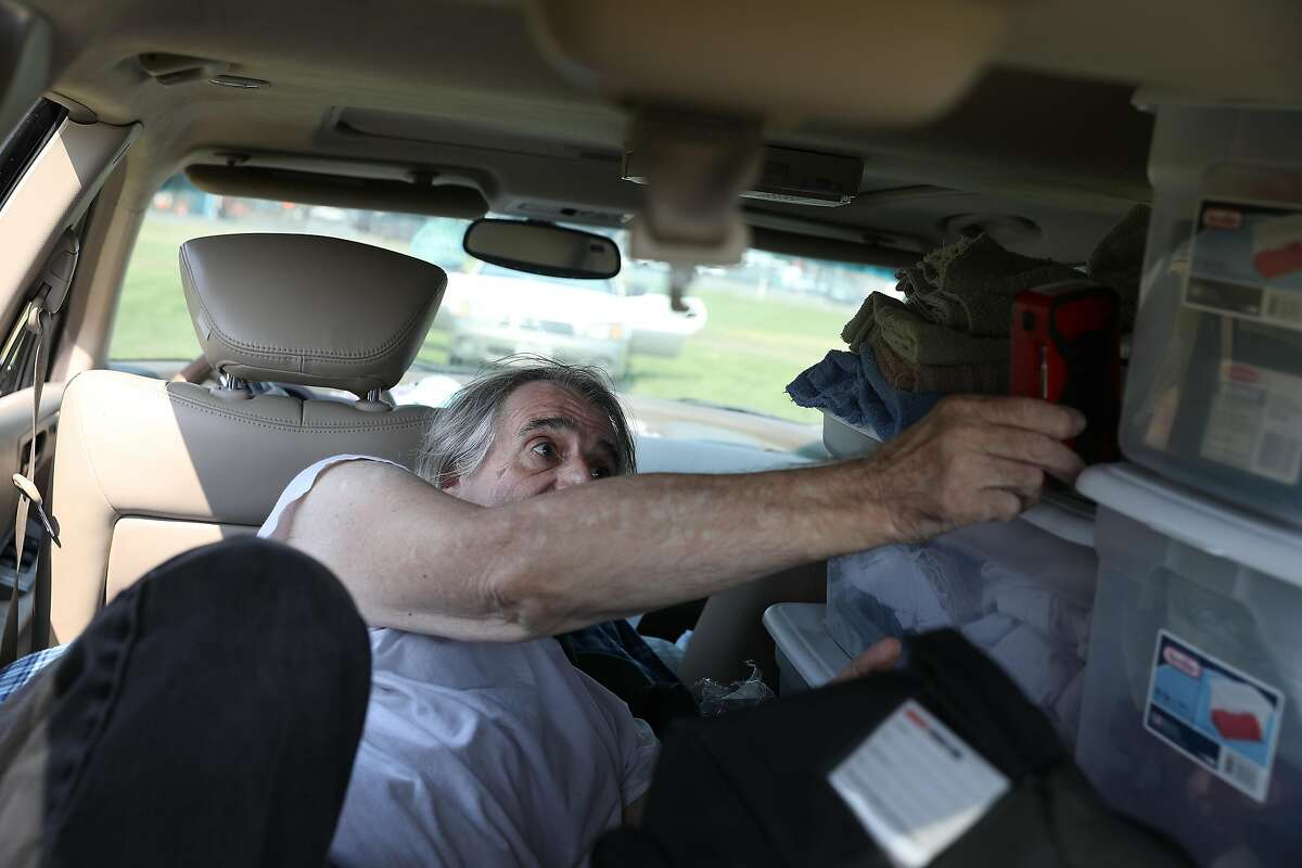 Steve Casa of Santa Rosa holds a Red Cross hand crank radio in his car at an evacuation center at the Sonoma Marin Fairgrounds, September 28, 2020.
