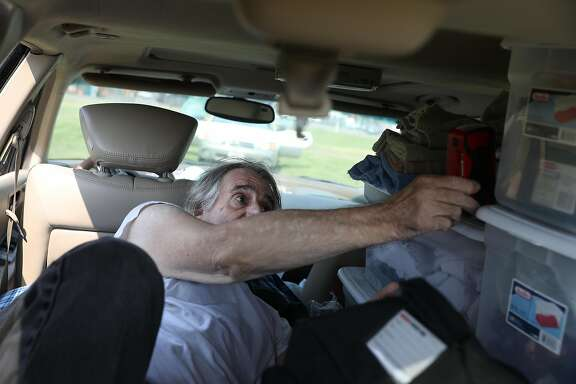 Steve Casa of Santa Rosa holds a Red Cross hand crank radio as he lays in his car at an evacuation center at the Sonoma Marin Fairgrounds and Event Center after evacuating during the night from his home on Monday, September 28, 2020 in Petaluma, Calif.  Casa said he was using the radio to listen to news updates to try to stay updated on his home.