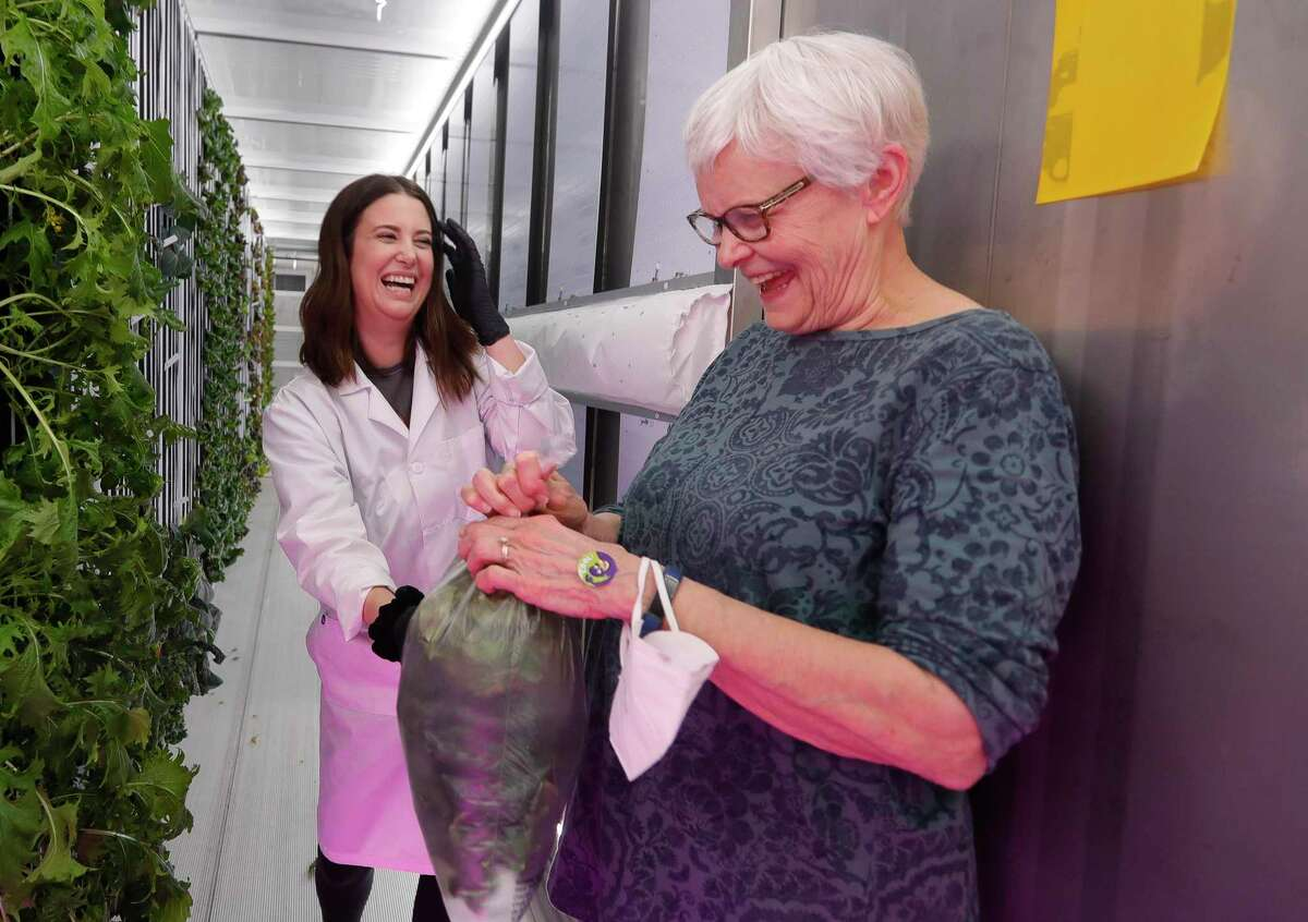 Alex Armstrong, left, shares a laugh with Jane Pope after handing her a bag of freshly harvested lettuce at Fare House Farms, a hydroponic farming operation, Wednesday, Sept. 23, 2020, in Oak Ridge. Hydroponic farming is a type of horticulture where indoor crops are grown without soil by using a nutrient-rich and climate controlled environment.
