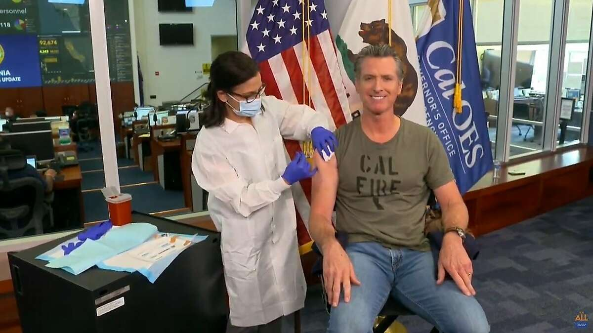 Gov. Gavin Newsom gets a flu shot during a news conference Monday, in this image taken from live streamed video from the California governor's office.