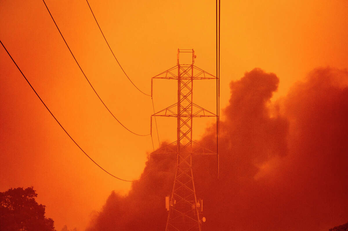 Smoke wafts past power lines as the Glass Fire burns in Santa Rosa, Calif., Monday, Sept. 28, 2020.