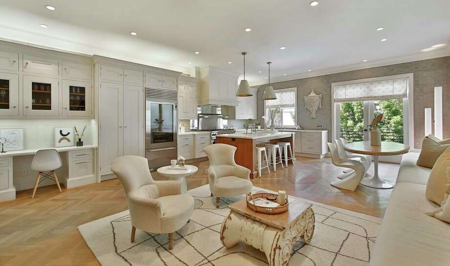 The open kitchen revolves around a marble-topped island and connects with a family room hosting an office area. Photo: Open Homes Photography