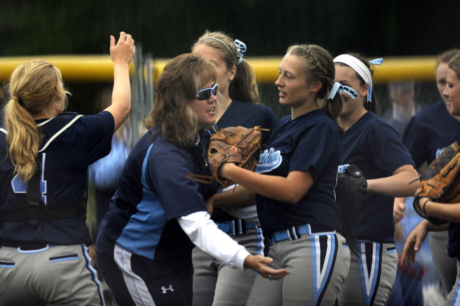 Meridian's Taylor Smith (foreground right) is greeted by her mother, Mustangs' coach Jamie Smith, following an inning-ending double play in a June 11, 2011 postseason game. Photo: Daily News File Photo