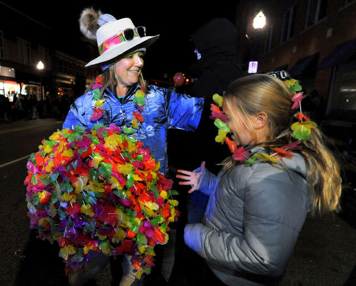 From 2017's Halloween Parade: Jackie Anderson of First Mid Bank and Trust, left, puts a leigh onto Brynn Hornbuckle, 11, during the Halloween parade in Edwardsville.