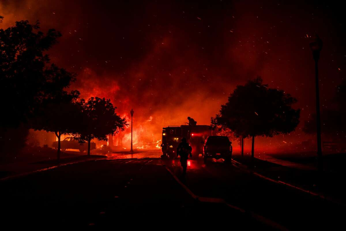Firefighters intervene while a home bursts into flames from the Shady Fire as it approaches Santa Rosa, on Sept. 28, 2020. The wildfire quickly spread over the mountains and reached Santa Rosa where it has begun to affect homes.