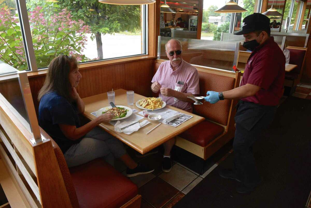 Patrick O'Brien, of Brookfield, has a birthday lunch with his wife Deborah at Elmer's Diner on Monday. Elmer's and other restaurants, will be permitted to open to 75 percent capacity inside beginning October 8 per Connecticut's phase three reopening rules. Monday, September 28, 2020, in Danbury, Conn. Waiter Anselmo Sedeno delivers their lunches.