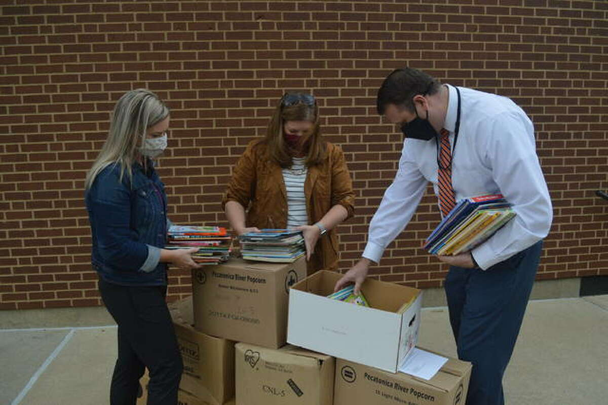 Left to right, Cari Wencewicz, a reading specialist for District 7; Lisa Grote from Junior Service Club of Edwardsville/Glen Carbon, and N.O. Nelson Elementary School Principal Andrew Gipson go through some of the books that were delivered to the school on Monday as part of the Junior Service Club's inaugural book donation drive.