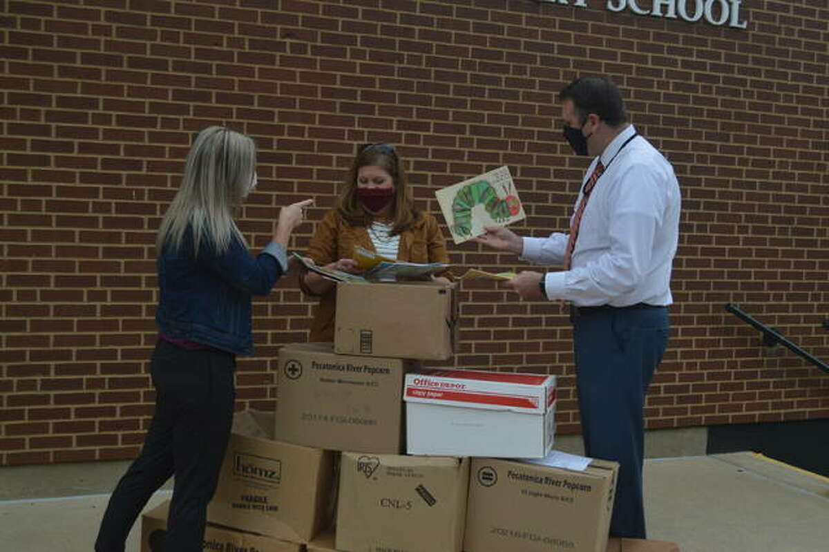 Left to right, Cari Wencewicz, a reading specialist for District 7; Lisa Grote from Junior Service Club of Edwardsville/Glen Carbon, and N.O. Nelson Elementary School Principal Andrew Gipson look at the titles of some of the books that were delivered to the school on Monday as part of the Junior Service Club's inaugural book donation drive.