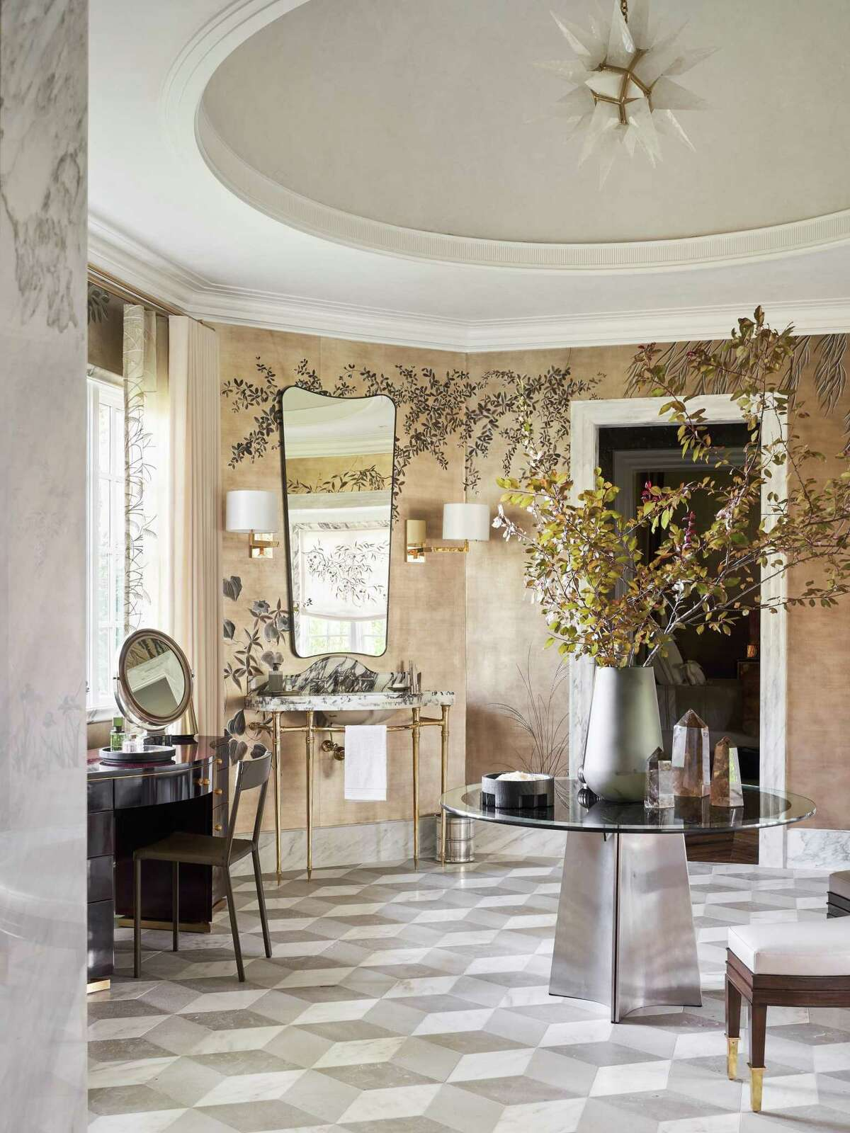 Doniphan Moore Interiors designed the primary bathroom, using de Gournay wallpaper and embroidered blinds made to match the floral design in the wallpaper. The Shade Store is a major sponsor and made all of the window treatments in the home.