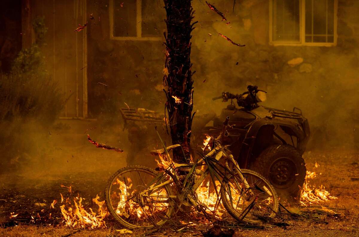 TOPSHOT - A bicycle and palm tree burn at a residence during the LNU Lightning Complex fire in the Spanish Flat area of Napa, California on August 18, 2020. - As of the late hours of August 18,2020 the Hennessey fire has merged with at least 7 fires and is now called the LNU Lightning Complex fires. Dozens of fires are burning out of control throughout Northern California as fire resources are spread thin. (Photo by JOSH EDELSON / AFP) (Photo by JOSH EDELSON/AFP via Getty Images)