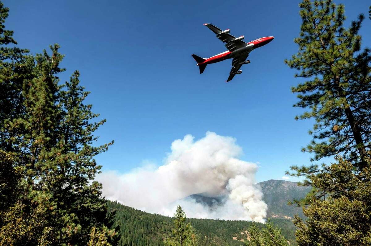 An air tanker prepares to drop retardant while battling the August Complex Fire in California's Mendocino National Forest on Sept. 17, one of two massive blazes that firefighters from Texas have been assigned to help control, (AP Photo/Noah Berger, File)