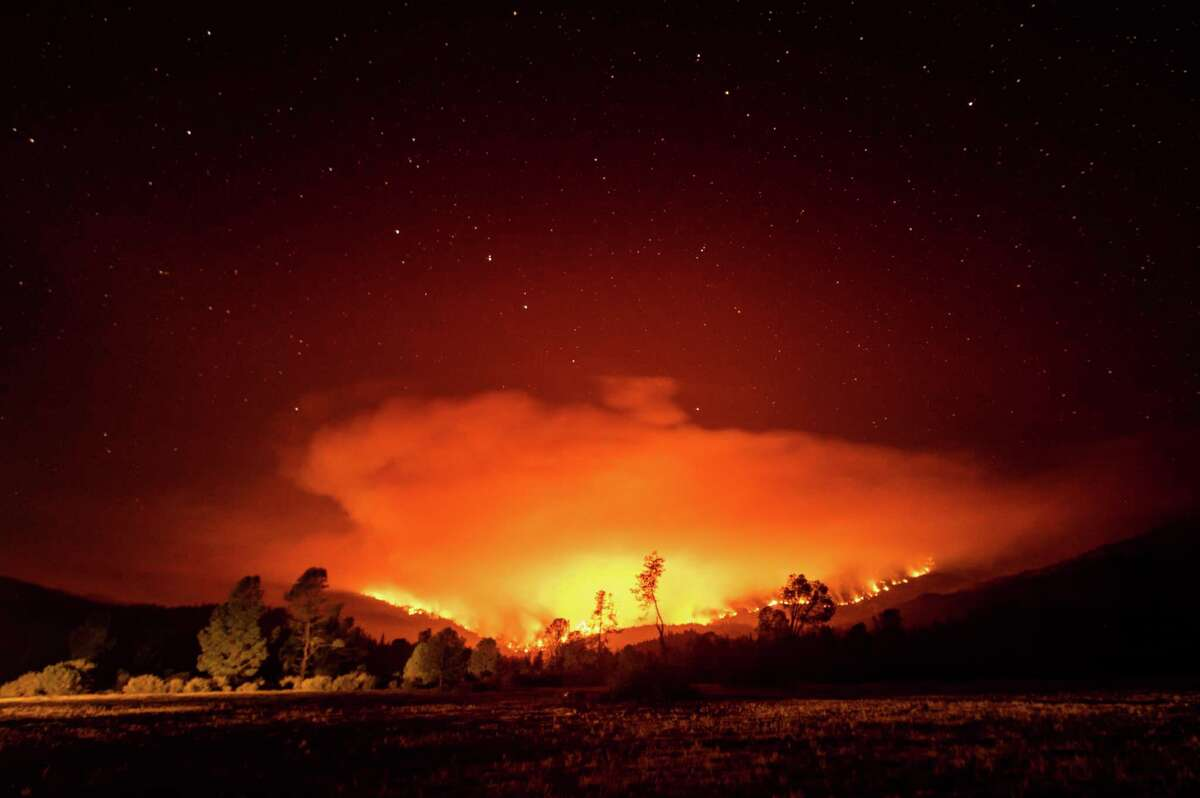 The August Complex Fire burns near Lake Pillsbury in California's Mendocino National Forest on Sept. 16. Teams on loan from Texas fire departments, including several in the San Antonio area, have been fighting it and the Creek Fire south of Yosemite National Park. (AP Photo/Noah Berger)