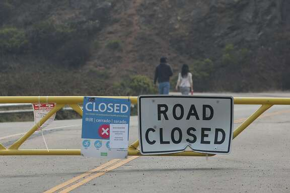 People are seen walking on Twin Peaks Boulevard beyond the road closure at the intersetion of Twin Peaks Boulevard and Burnett Avenue on Monday, August 31, 2020 in San Francisco, Calif.
