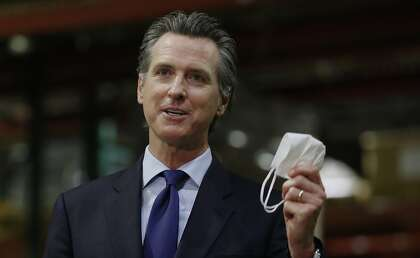 In this June 26, 2020 file photo, Gov. Gavin Newsom holds a face mask as he urges people to wear them to fight the spread of the coronavirus during a news conference in Rancho Cordova, Calif.