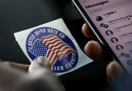 Drew William, a sophomore from Prairie View A&M University, looks at the sticker he received after voting at the Waller County Courthouse during early voting Wednesday, Oct. 24, 2018, in Hempstead. On the ride back to campus, William proudly called his father and texted friends encouraging them to vote.