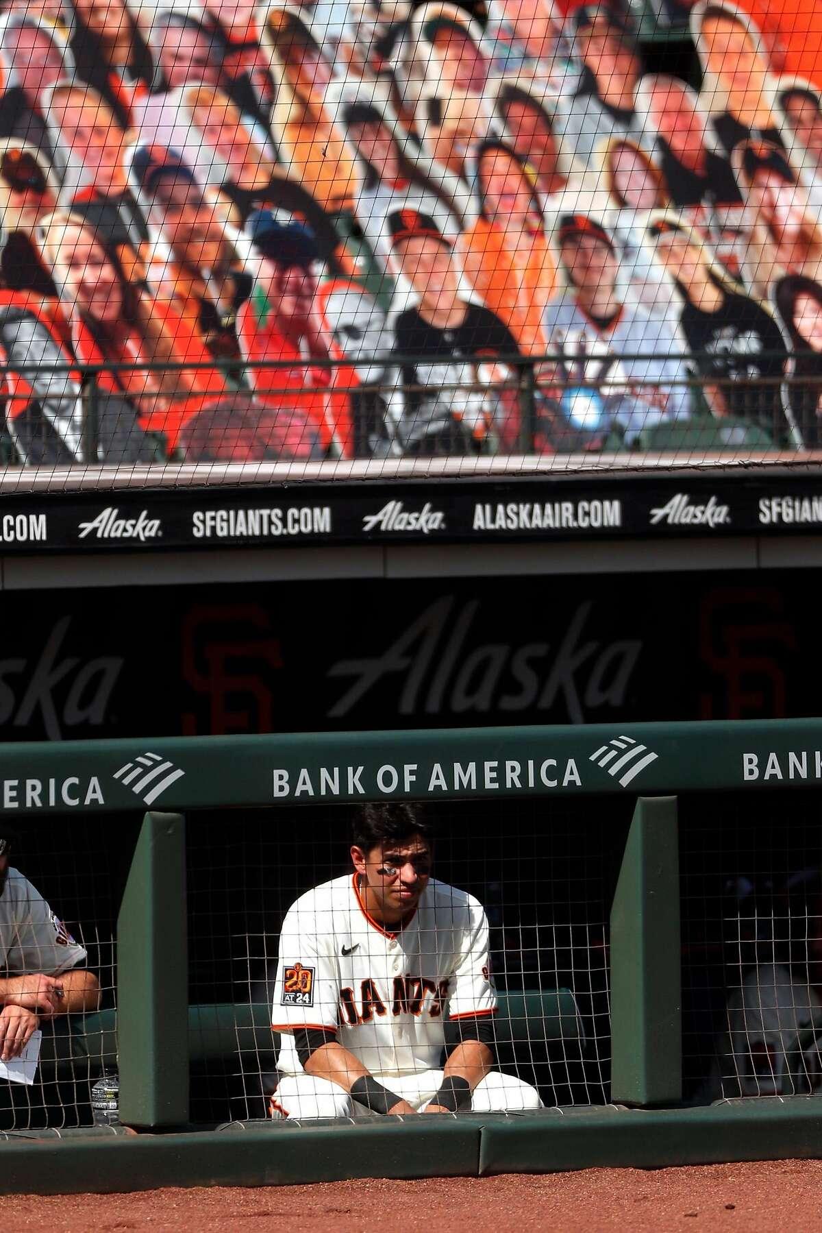 The Giants' Mauricio Dubón sits below several cardboard cutouts at Oracle Park.