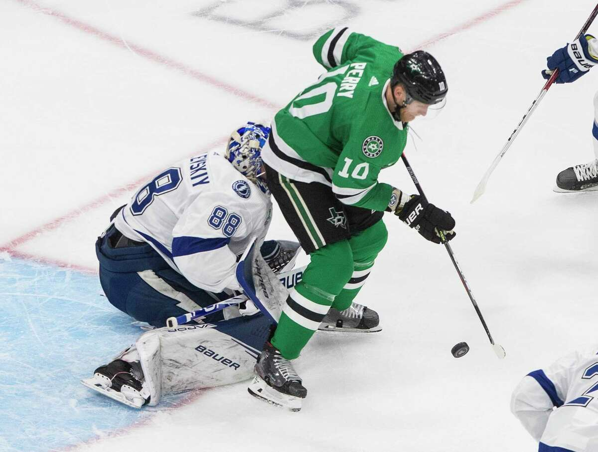 Tampa Bay Lightning goalie Andrei Vasilevskiy (88) makes a save as Dallas Stars' Corey Perry (10) interferes during second-period NHL Stanley Cup finals hockey game action in Edmonton, Alberta, Monday, Sept. 28, 2020. (Jason Franson/The Canadian Press via AP)