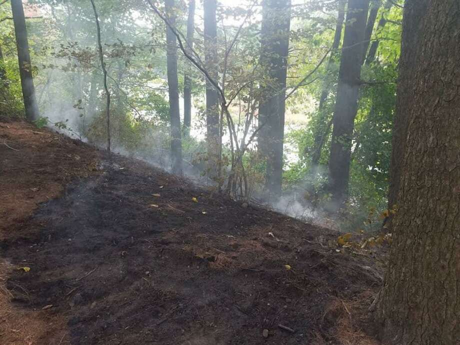 Firefighters had to stretch over 1,000 feet of hose to extinguish a brush fire on private property in Hamden, Conn., on Monday, Sept. 28, 2020. Photo: Contributed Photo / Hamden Fire Department