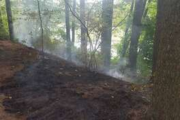 Firefighters had to stretch over 1,000 feet of hose to extinguish a brush fire on private property in Hamden, Conn., on Monday, Sept. 28, 2020.